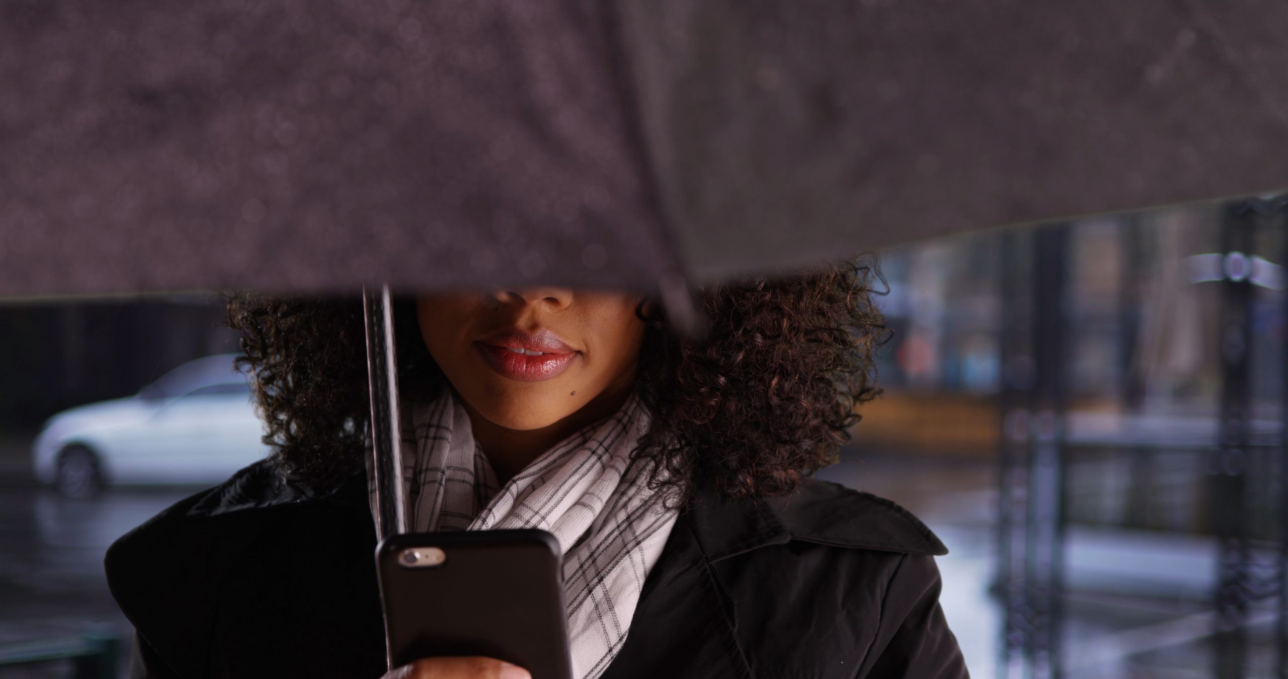 mysterious,african,woman,with,umbrella,checking,mobile,device,in,the